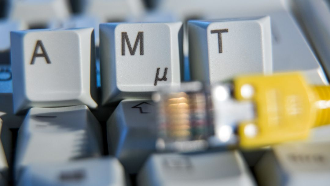 """Der Schriftzug """"Amt"""" ist auf einer Computertastatur hinter einem Netzwerkkabel zu sehen."""