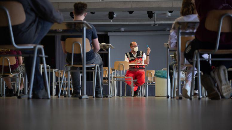 Ein Mitarbeiter des DRK erklärt Schülern und Schülerinnen einer Abschlussklasse den Corona-Test. | Bild:dpa-Bildfunk/ Sebastian Gollnow/
