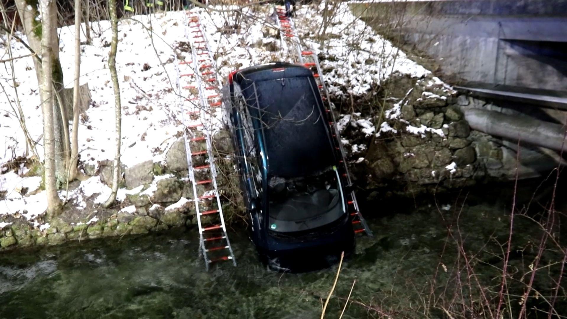 Ein Auto wird mit Leitern aus einem Bach geborgen.