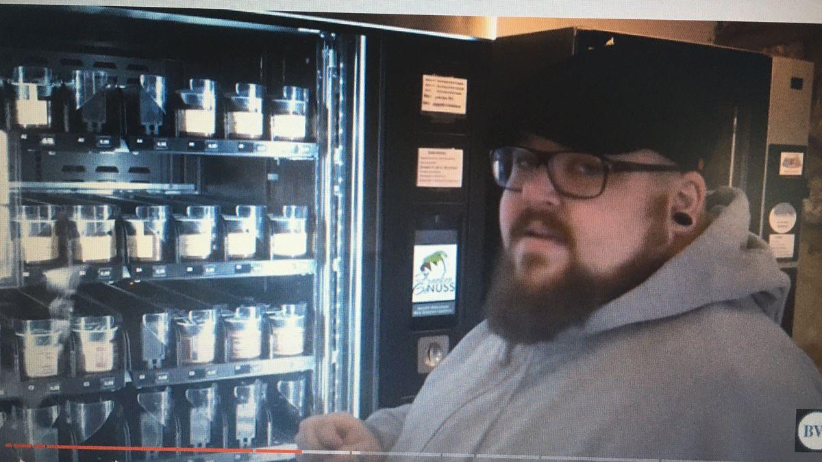 Mann steht vor einem Lebensmittelautomaten