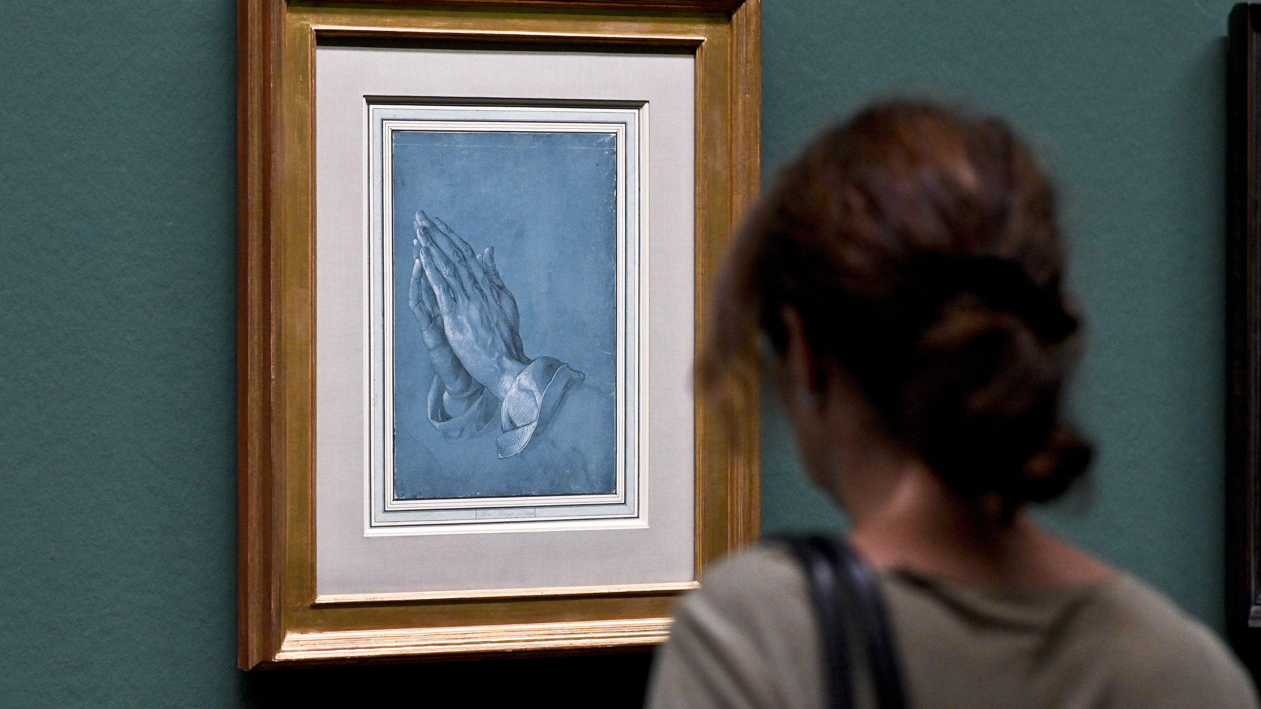 """Eine Besucherin steht vor den """"Betenden Händen"""", eine Zeichnung auf hellblauem Grund"""