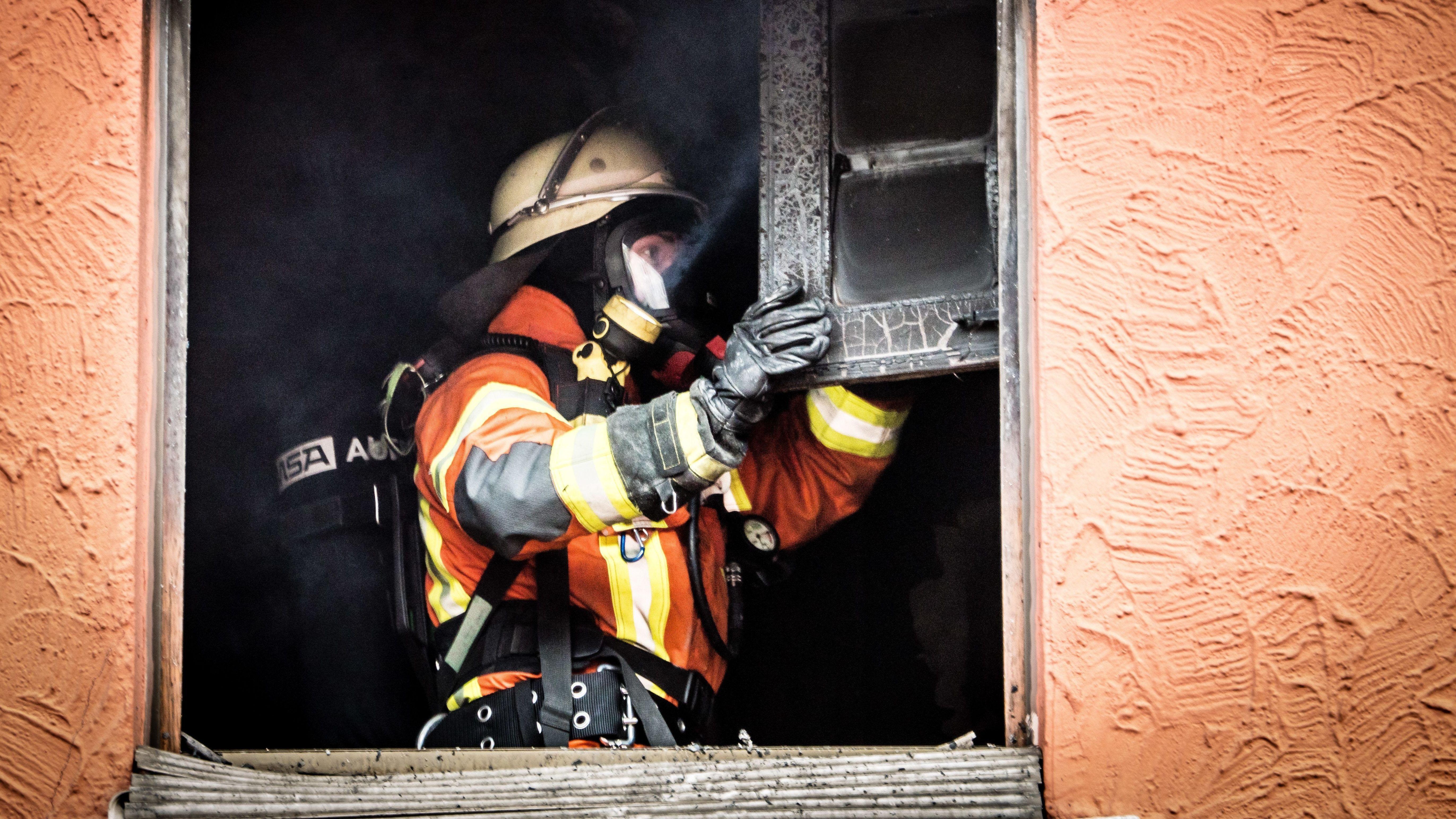 Ein Feuerwehrmann steht in einer Wohnung und kontrolliert einen verbrannten Schrank.