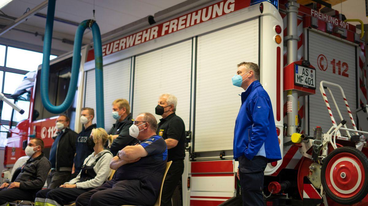 Feuerwehrkräfte sitzen vor einem Löschzug in einer Halle und schauen in Richtung eines Monitors.