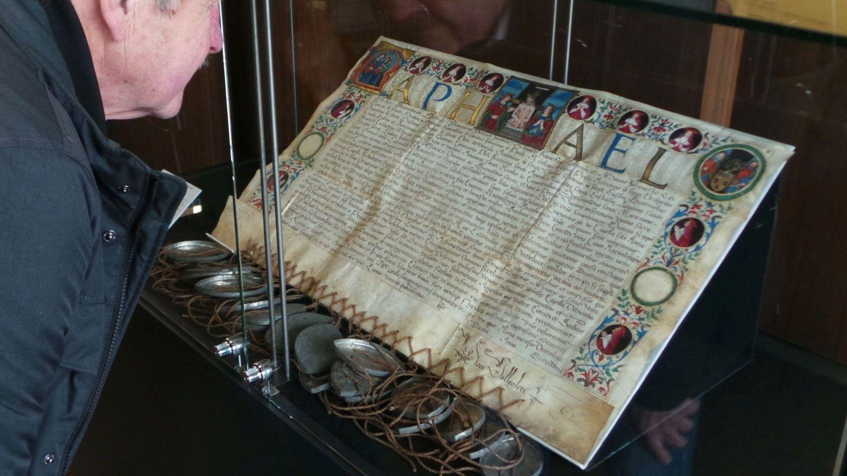 Ein Ausstellungsbesucher schaut sich eine Urkunde in einer Vitrine an.