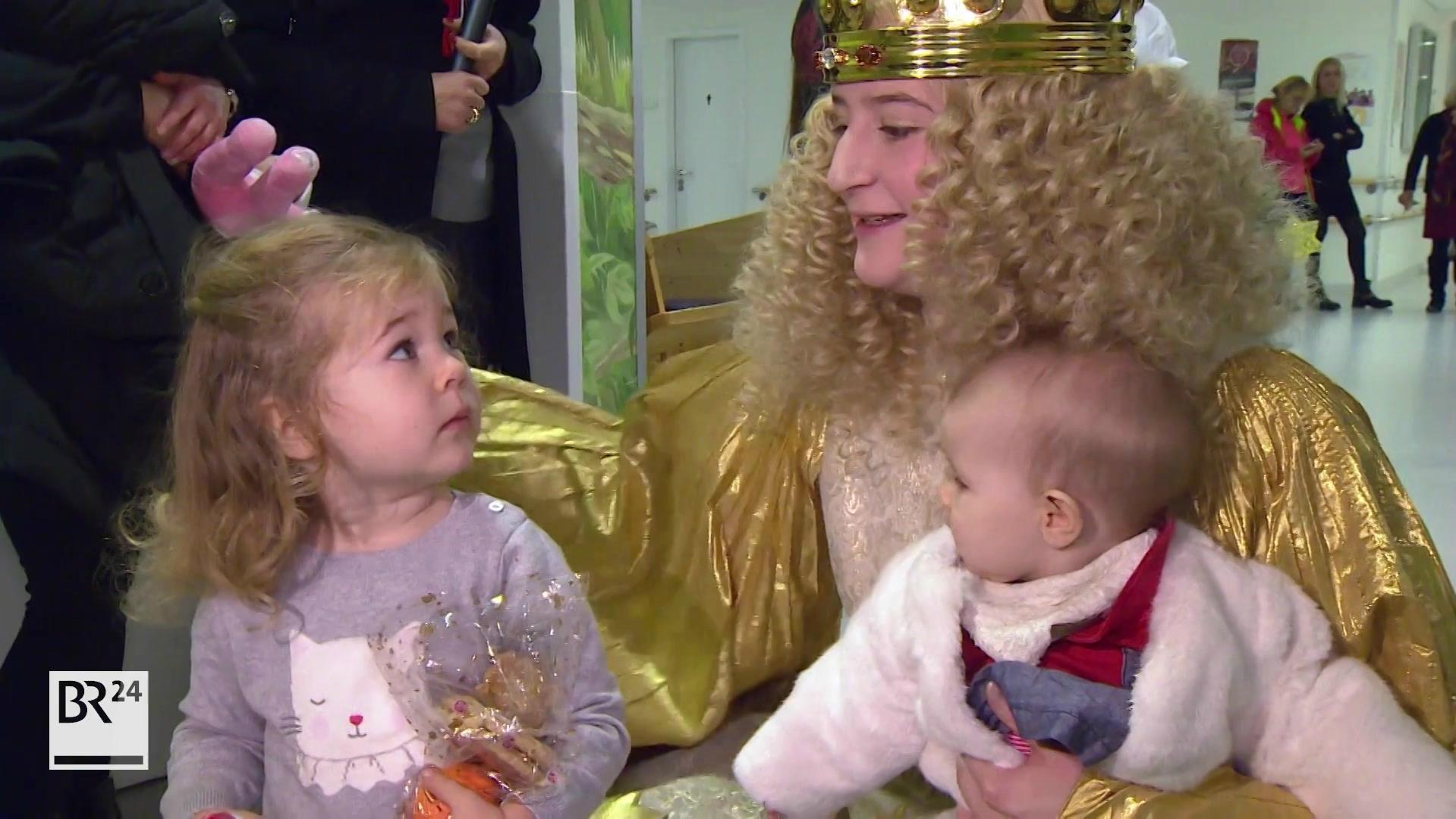 Christkind mit zwei Kleinkindern auf dem Schoß