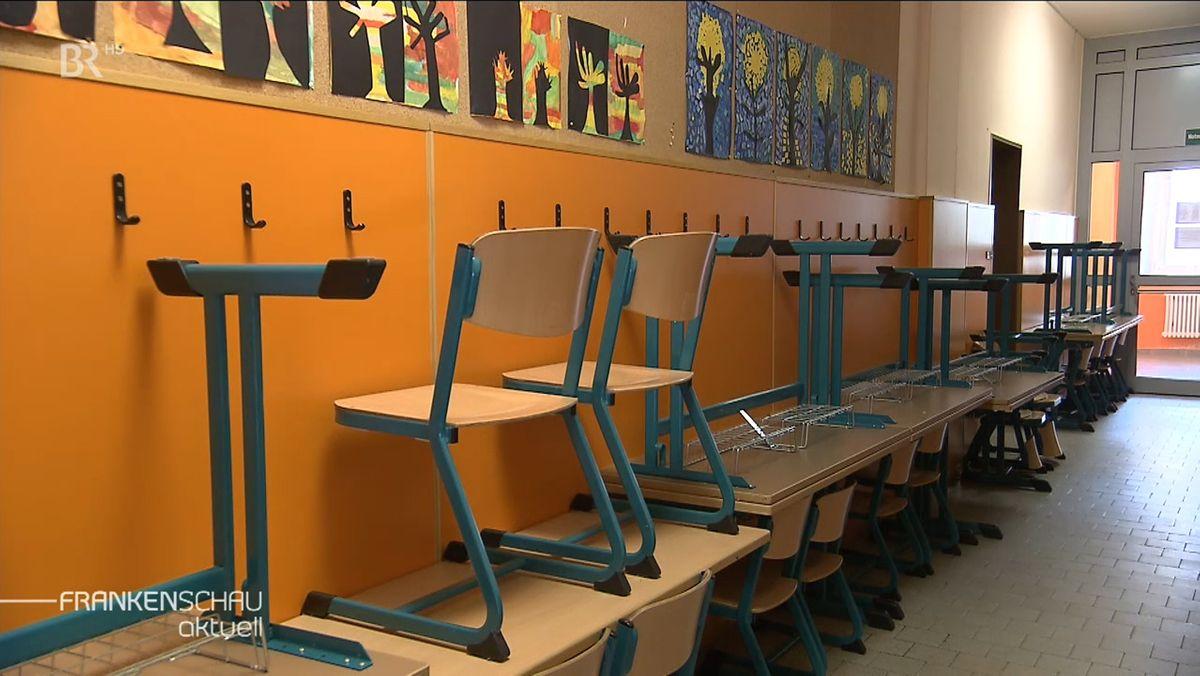 Stühle stehen auf Schulbänken