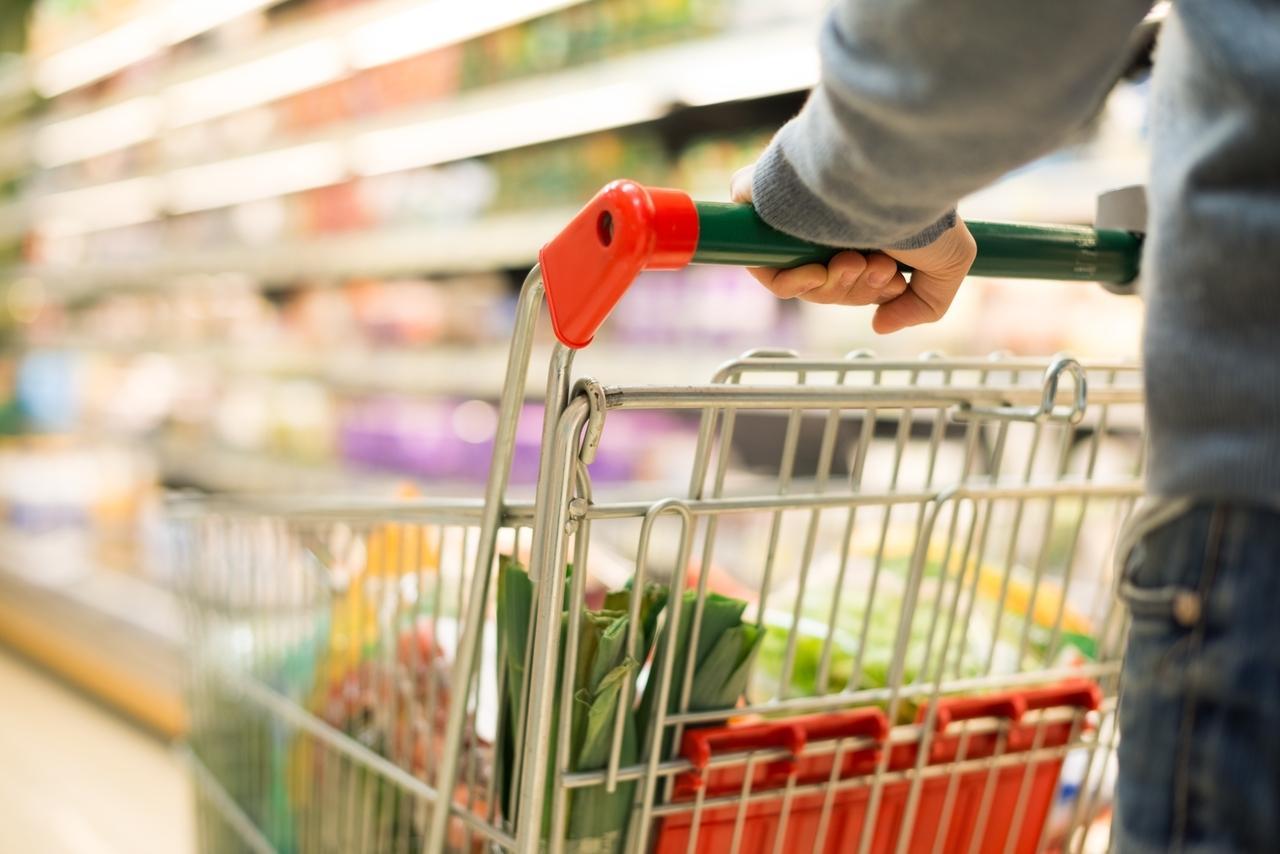 Ein gefüllter Einkaufswagen in einem Supermarkt.