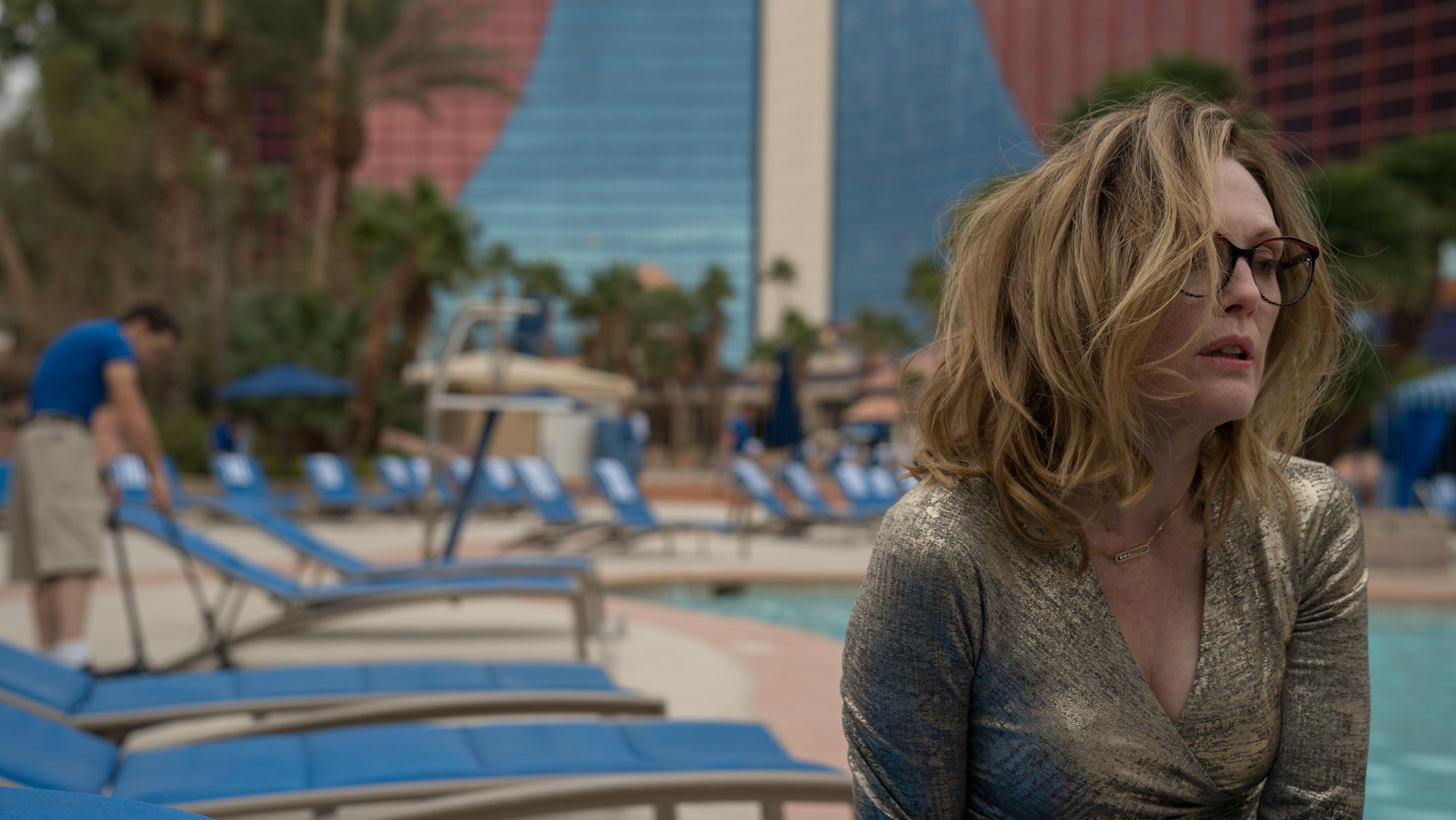 Julianne Moore sitzt mit zerzausten Haaren an einem Hotel-Swimmingpool und blickt ins Leere