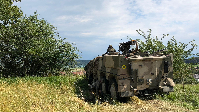 Bei der Brigadegefechtsübung «Berglöwe 2018» steht ein Fahrzeug der Bundeswehr auf einer Wiese.