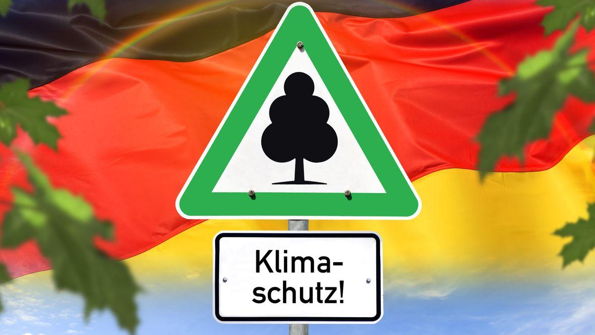 Schild mit Aufschrift Klimaschutz vor Deutschlandfahne