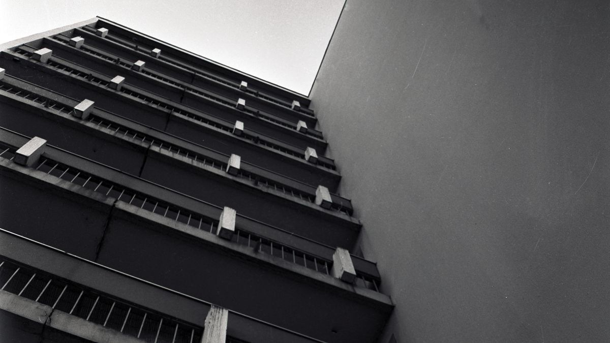 Blick von unten auf graue Betonbalkone eines Hochhauses