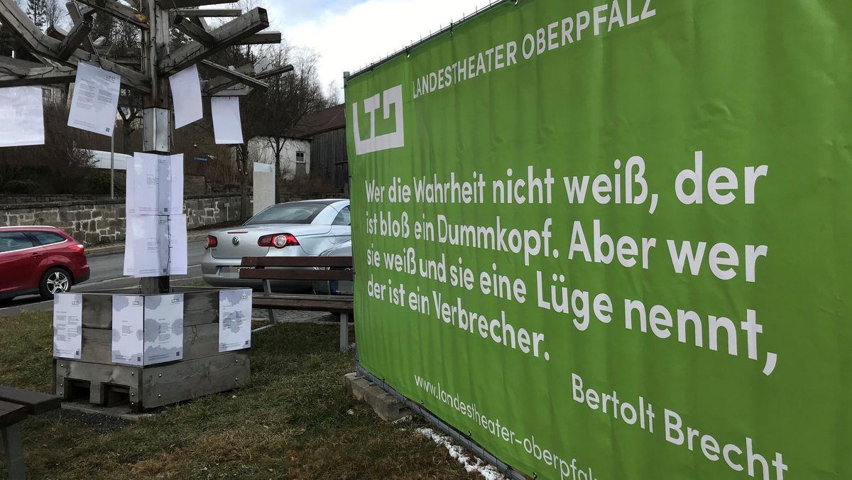 Banner mit Brecht-Zitat vor dem Rathaus in Flossenbürg, links daneben ein Holzbaum mit Lyrik.