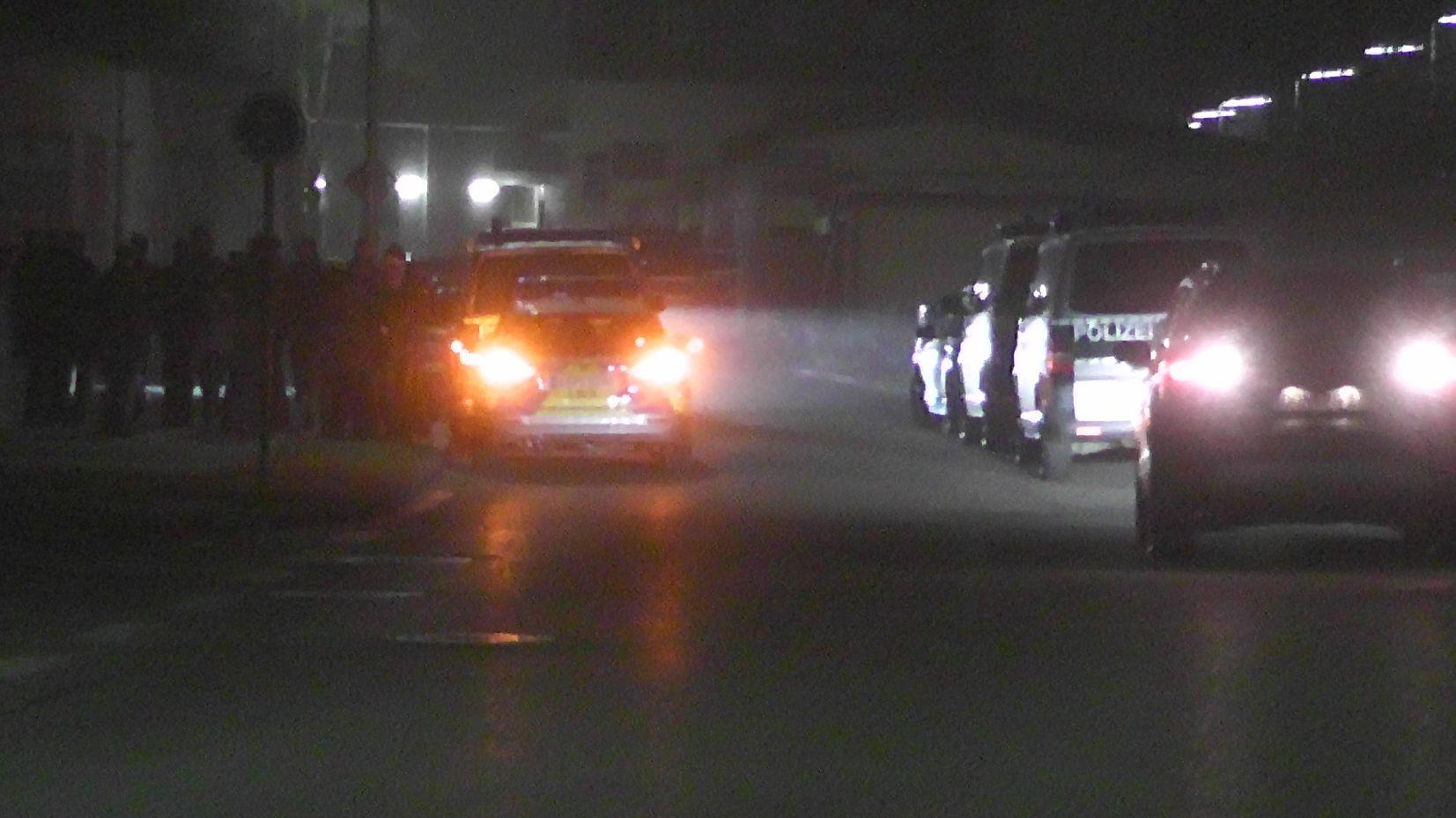 Mehrere Polizeiautos stehen an der Straße, daneben viele Polizisten