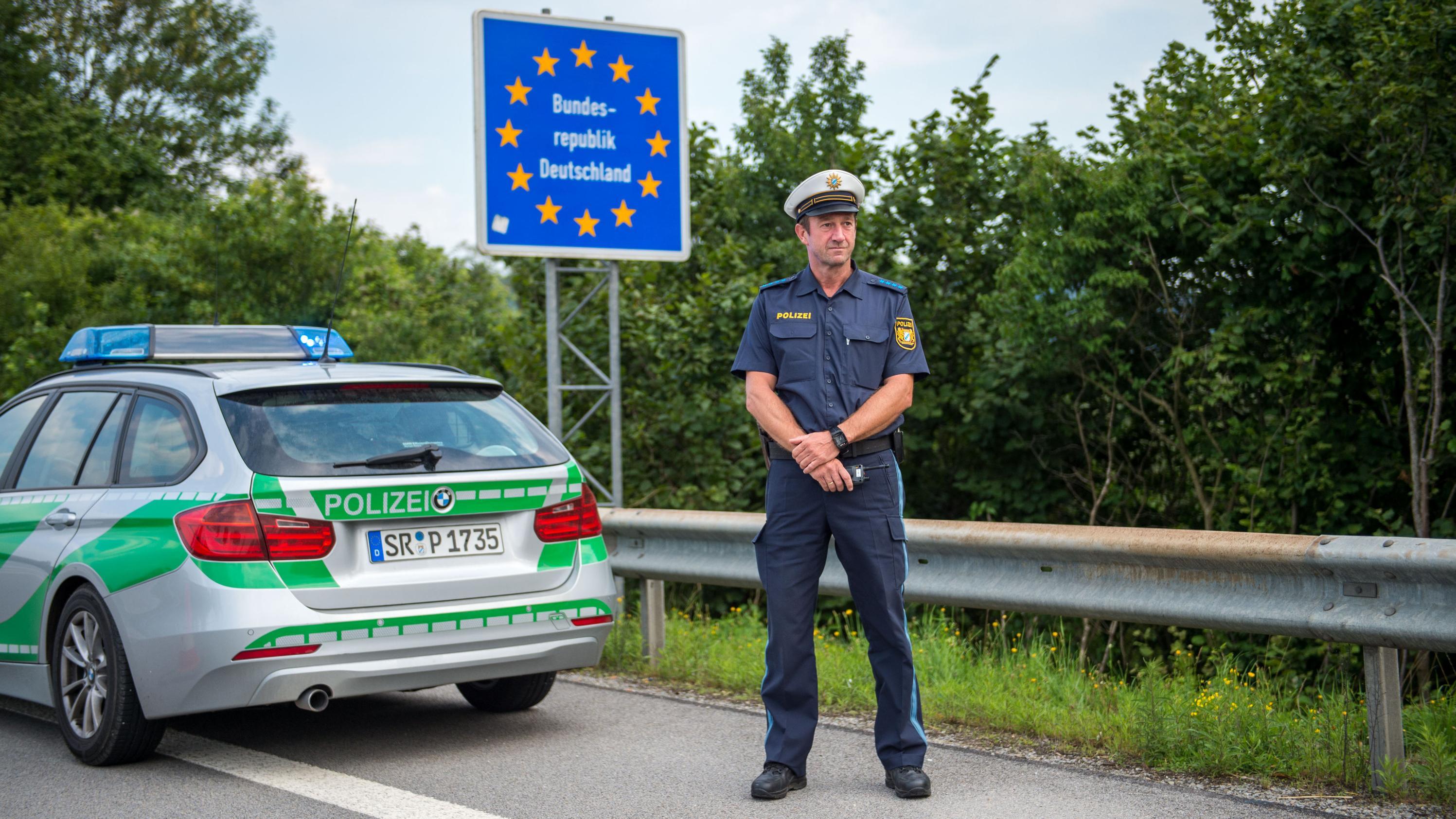 Ein Polizist steht am Straßenrand hinter seinem Auto und vor einem Grenzschild der Bundesrepublik