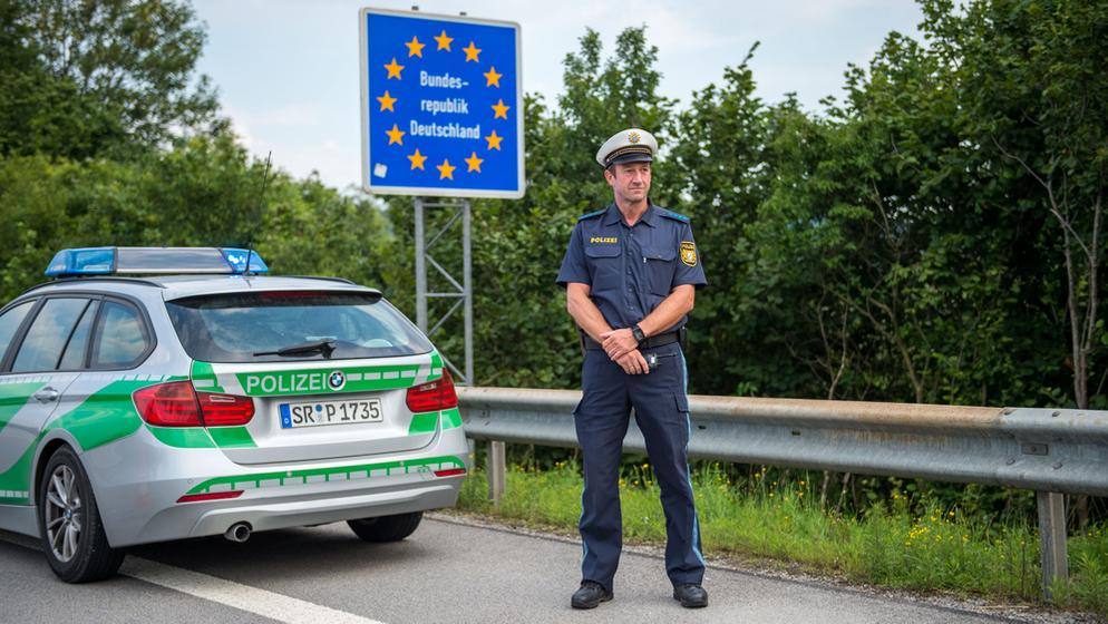 Ein Polizist steht am Straßenrand hinter seinem Auto und vor einem Grenzschild der Bundesrepublik | Bild:dpa-Bildfunk / Lino Mirgeler