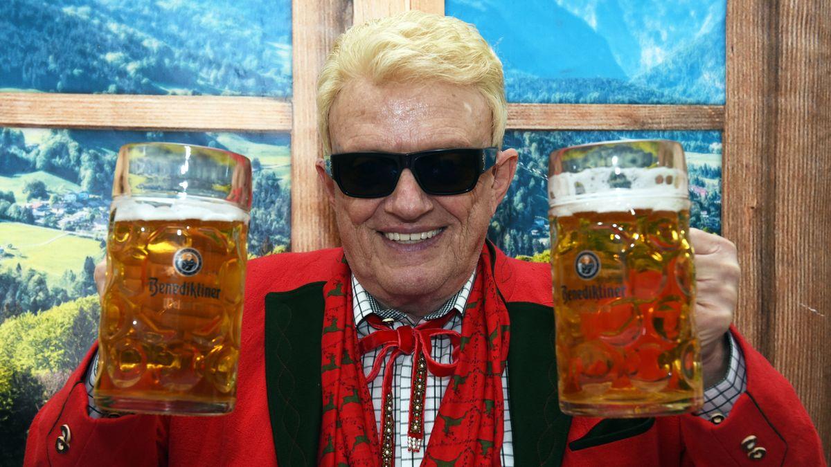 Der Sänger mit zwei gefüllten Bierkrügen in der Hand