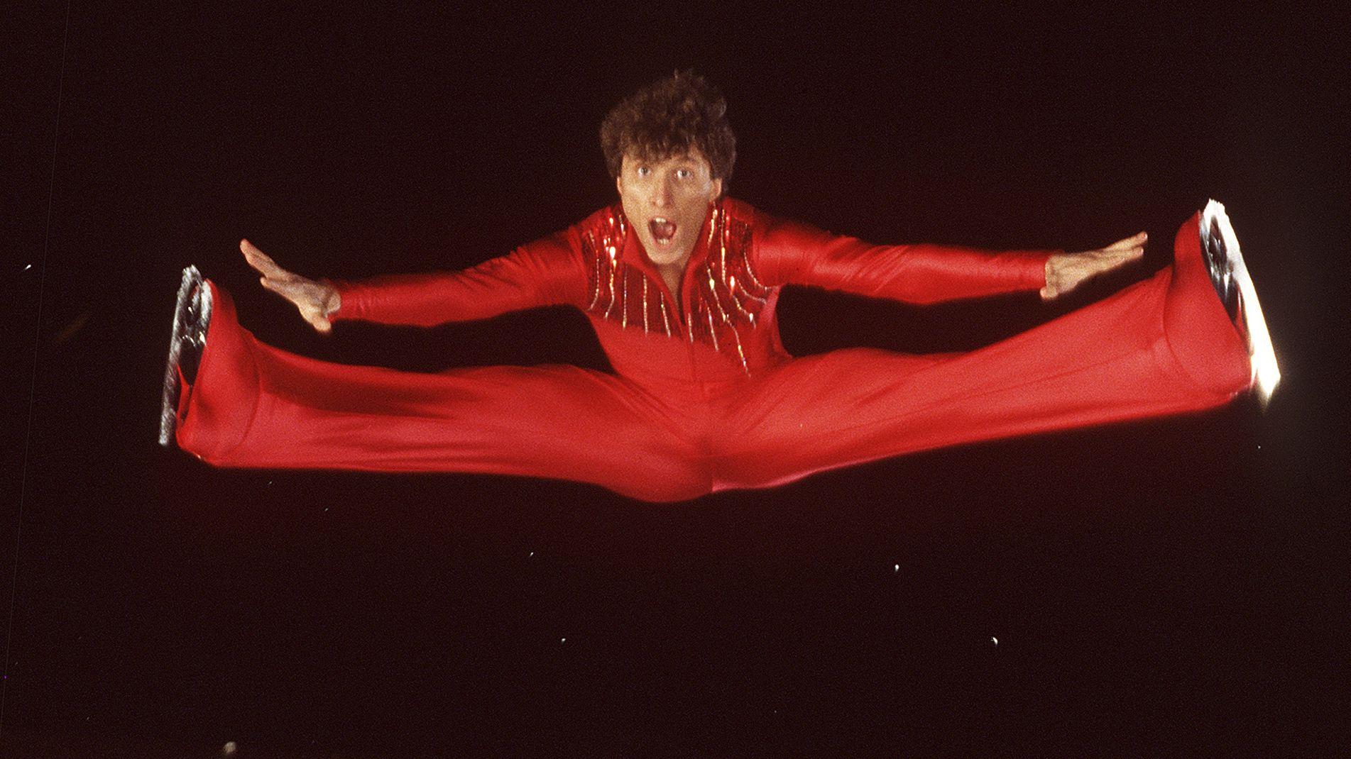 Norbert Schramm zeigt in seinem feuerroten Eiskunstlauf-Anzug einen Sprung