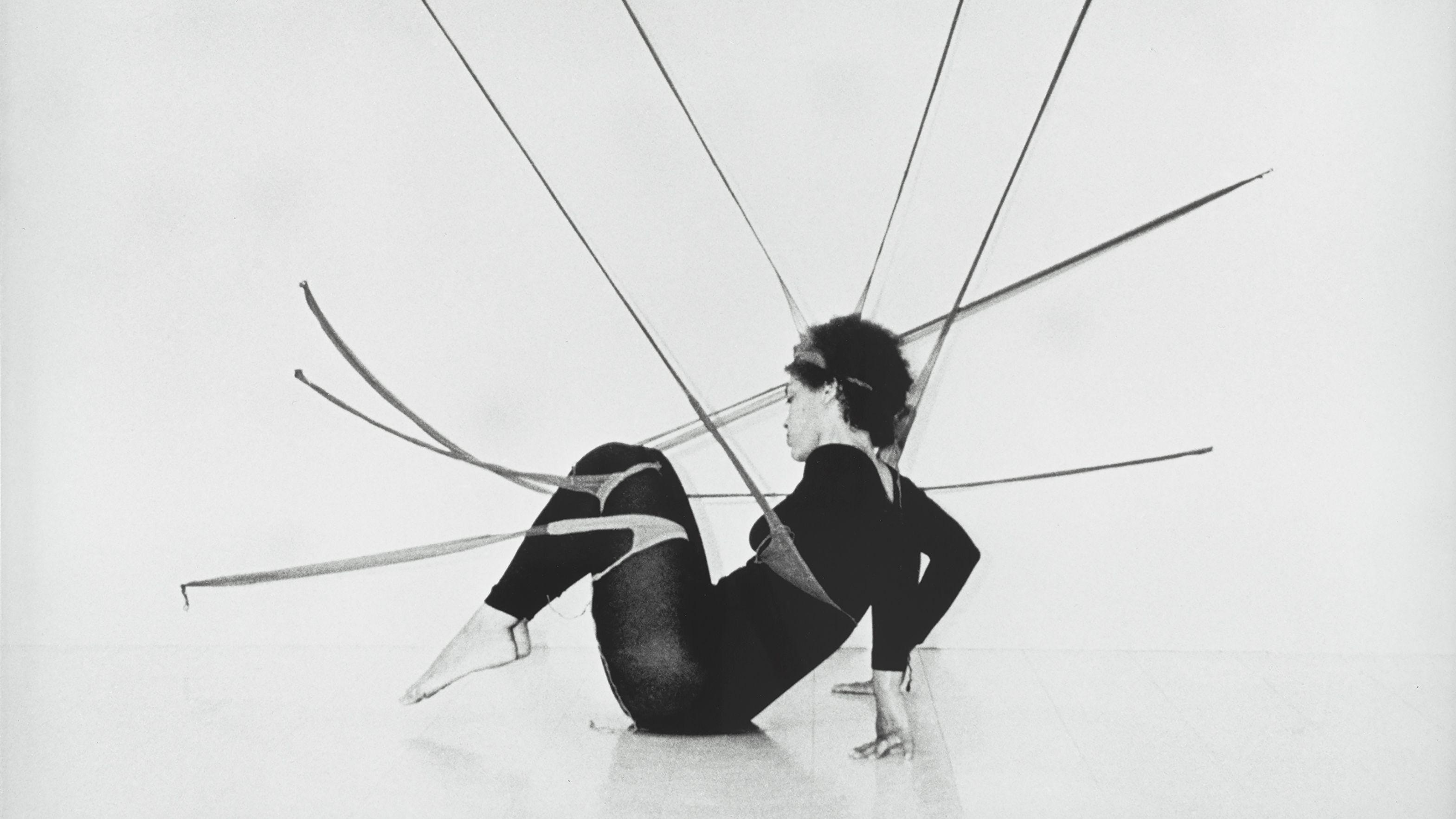 Die Performerin Maren Hassinger sitzt vor einer Wand am Boden, sie hängt in einem tentakelähnlichen Geflecht aus Seidenstrümpfen