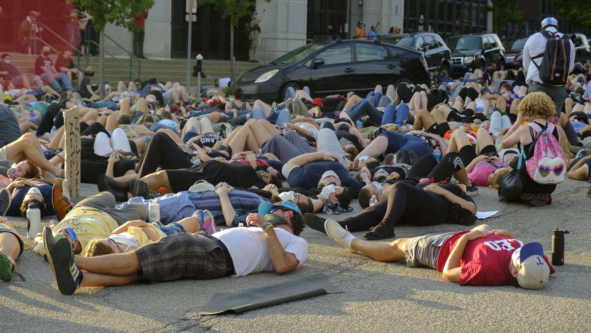 Demonstrierende liegen auf einer Straße.
