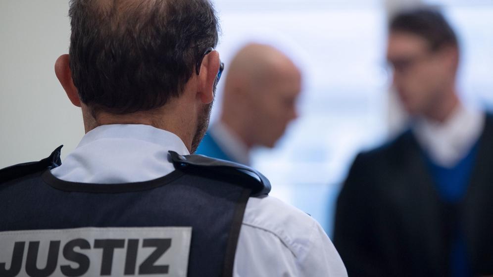 Ravensburg: Der angeklagte mutmaßliche Supermarkt-Erpresser (Mitte) geht während des Prozesses in Saal 1 des Landgerichts an seinen Platz. | Bild:dpa-Bildfunk/Marijan Murat