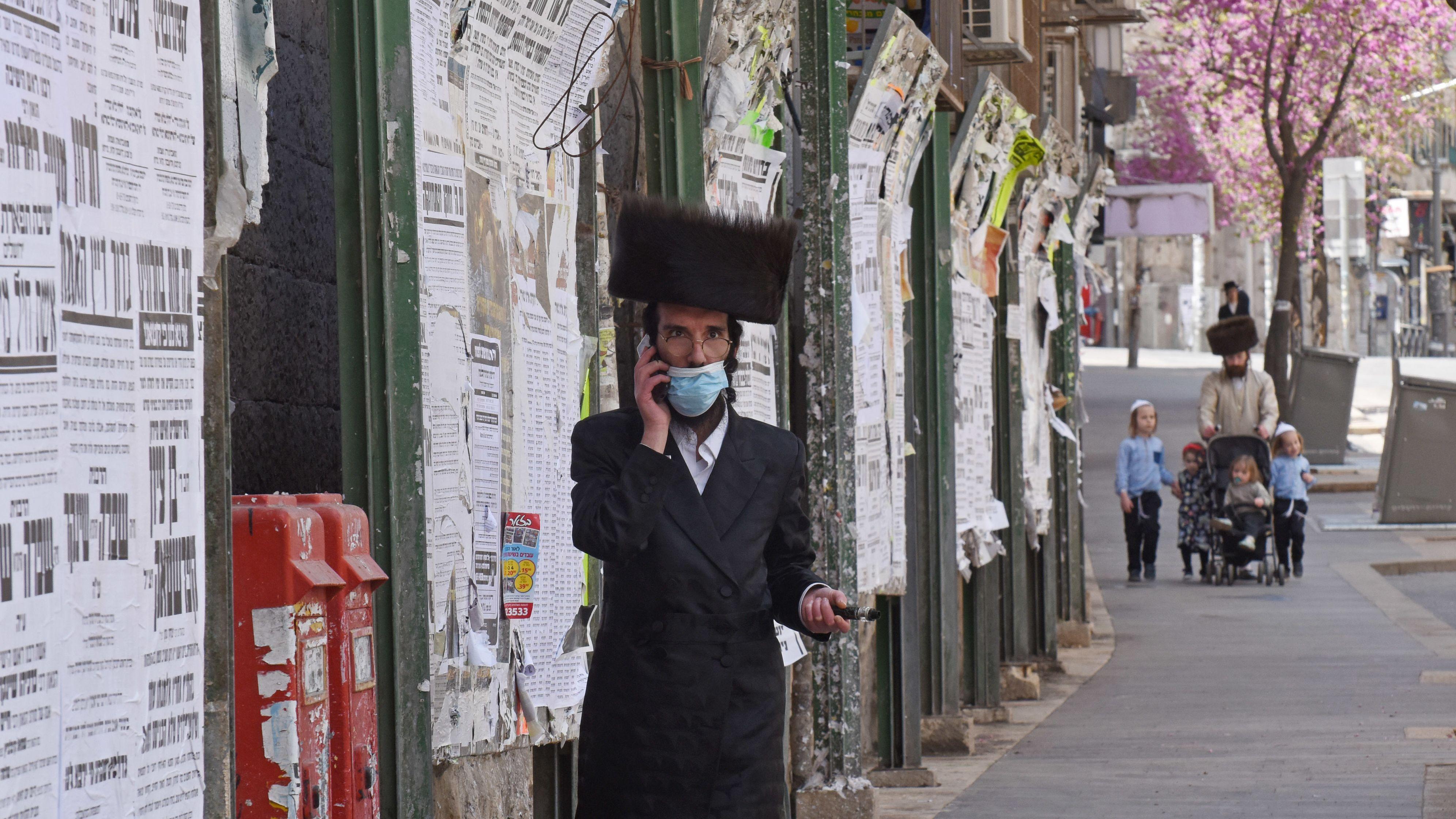 Ein jüdisch-orthodoxer Mann mit Mundschutz und Smartphone. Die israelische Regierung setzt im Kampf gegen das Coronavirus auf Handytracking.