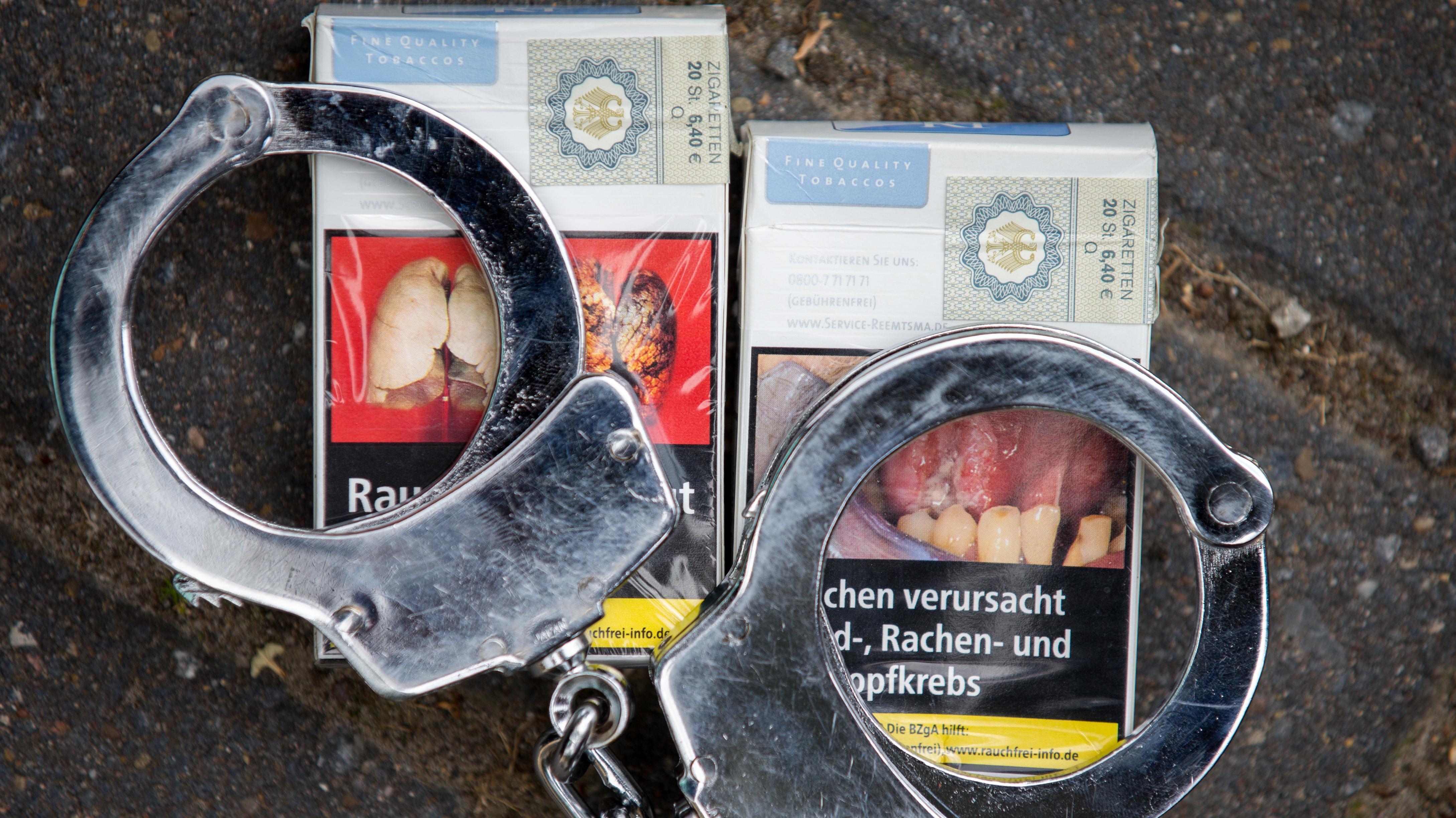 Ein Paar Handschellen liegt auf zwei Zigarettenpackungen.