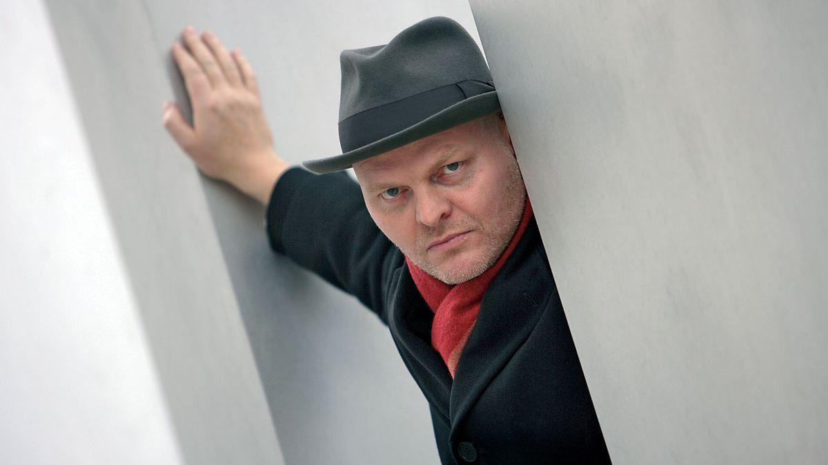Porträt des Autors Hallgrímur Helgason mit Hut und rotem Schal zwischen weißen Mauern