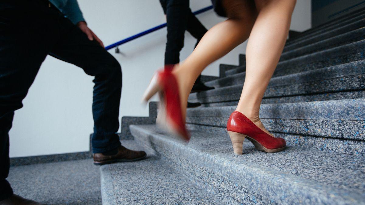 Eine Frau und zwei Männer gehen eine Treppe hinauf.