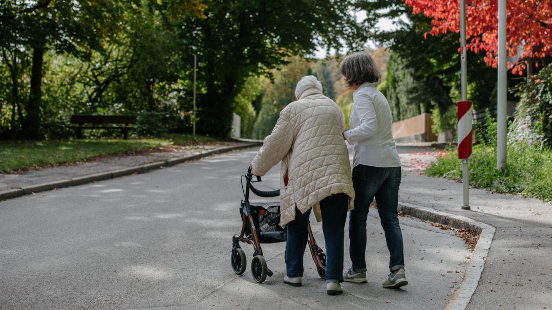Eine Pflegerin hilft einer Seniorin mit Rollator über die Straße.