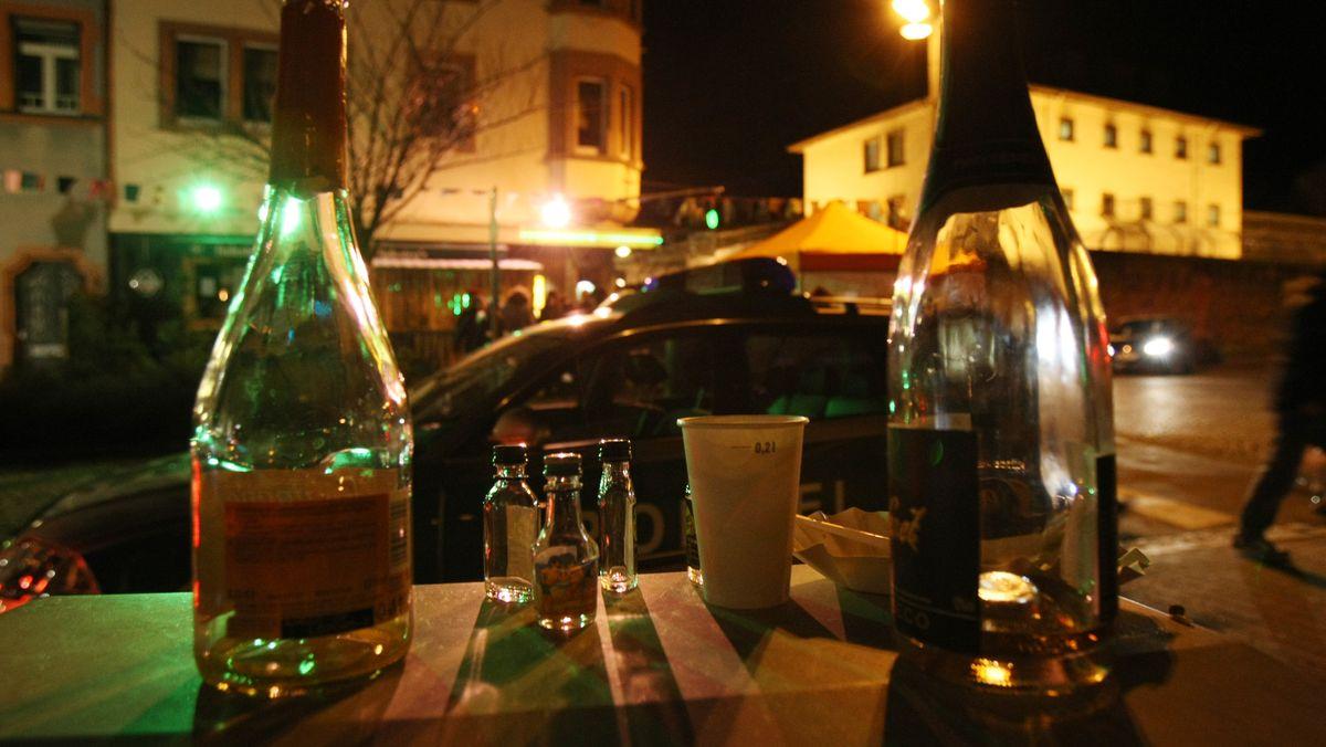 Leere Flaschen stehen vor einer Kneipe, an der ein Polizeiauto vorbei fährt (Symbolbild)