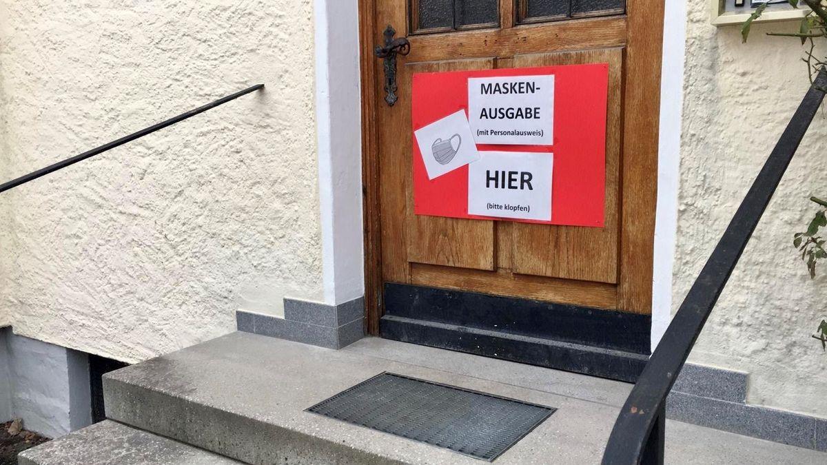 Eigens installierter Ausgabeschalter in der St.-Jakobs Apotheke Buchbach im Lkr. Mühldorf am Inn - ein Kunde holt sich kostenlose Masken ab.