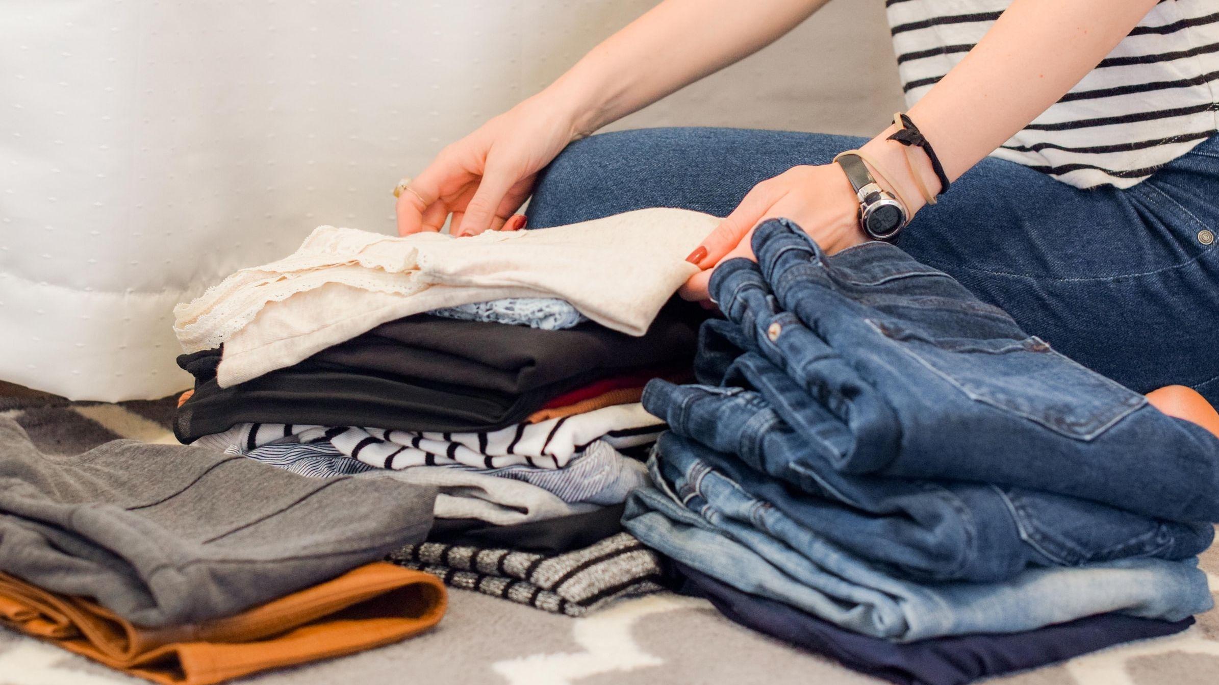Frau ordnet Kleidungsstapel