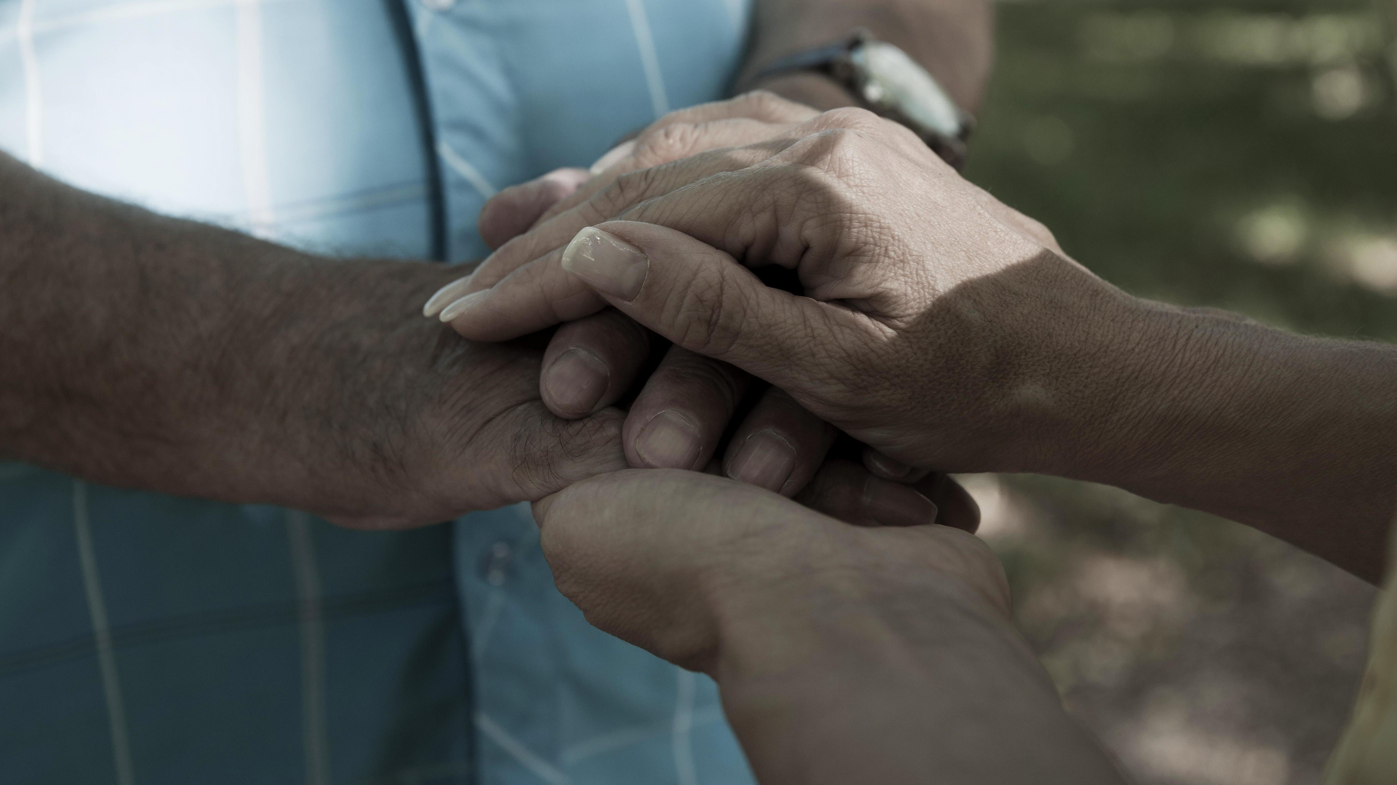 Mann und Frau legen ihre Hände aufeinander