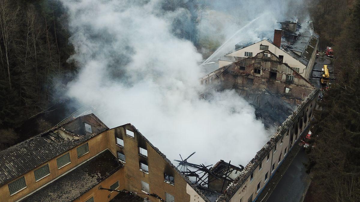 Aus zwei ausgebrannten Gebäude ohne Dach steigt dichter Rauch.