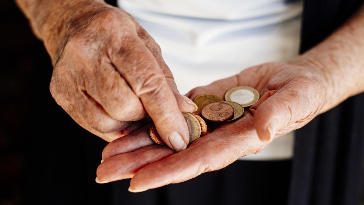Eine alte Frau mit Geldmünzen in der Hand.