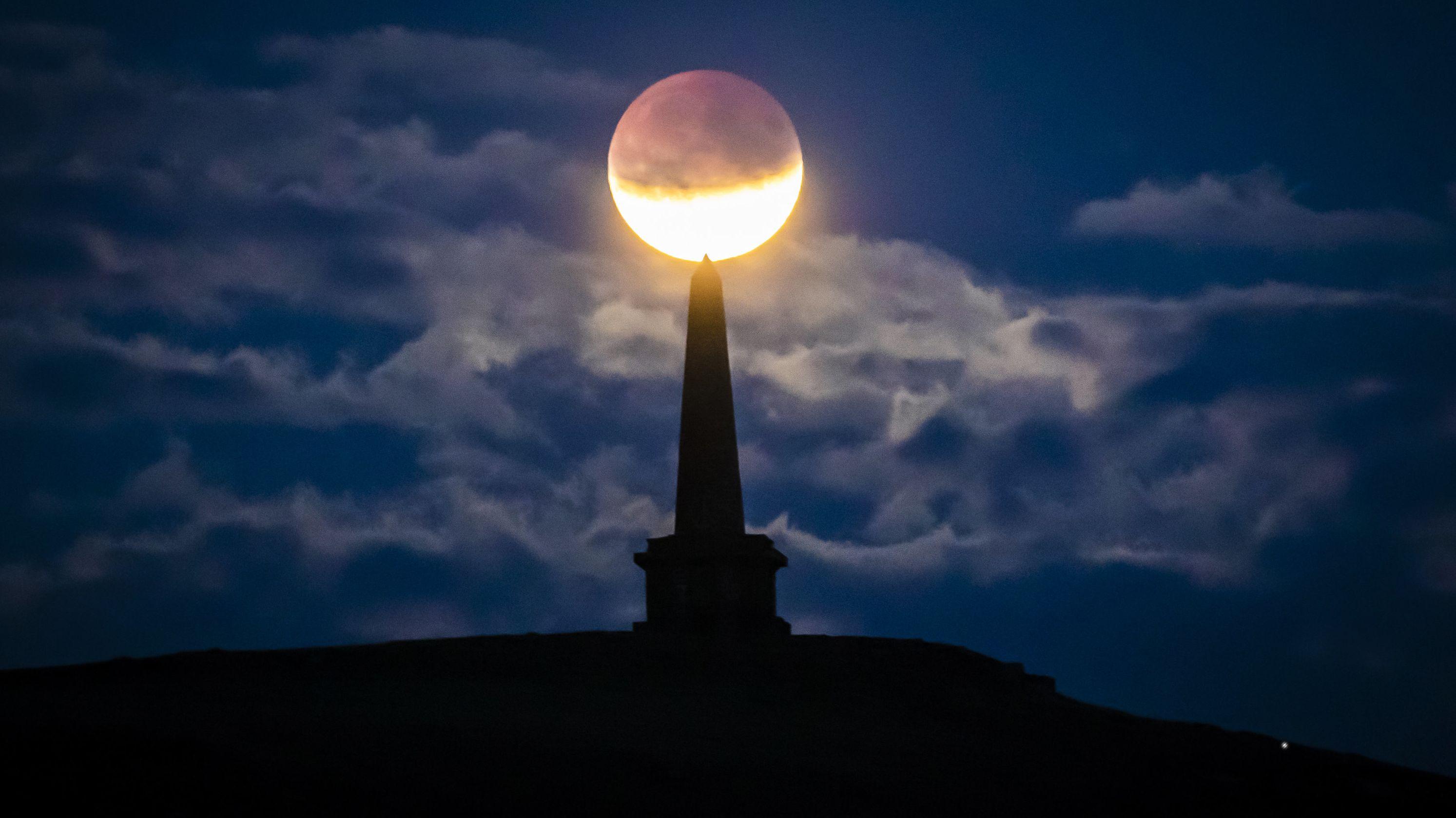 Großbritannien, Todmorden: Der Mond ist während einer partiellen Mondfinsternis hinter dem Denkmal Stoodley Pike zu sehen.