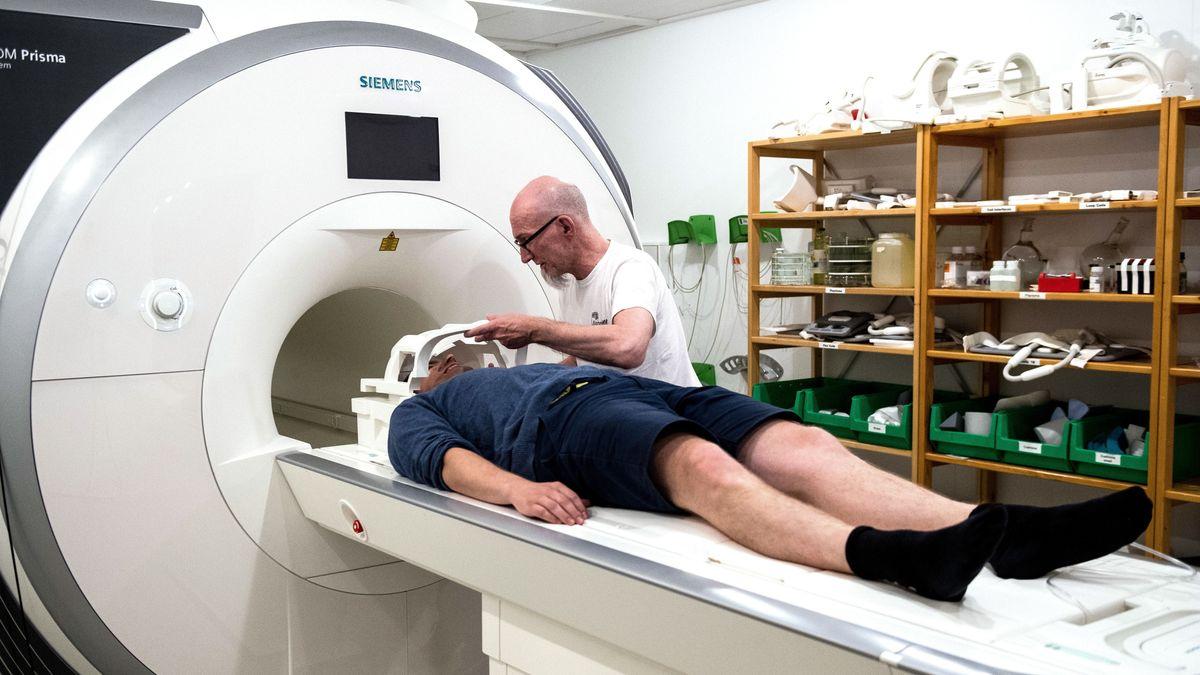 Die Mitarbeiter des Göttinger Biophysikers Jens Frahm, Volkert Roeloffs (l) und Kurt Böhm, legen eine Kopfspule an einem Magnetresonanztomograph (MRT) an.