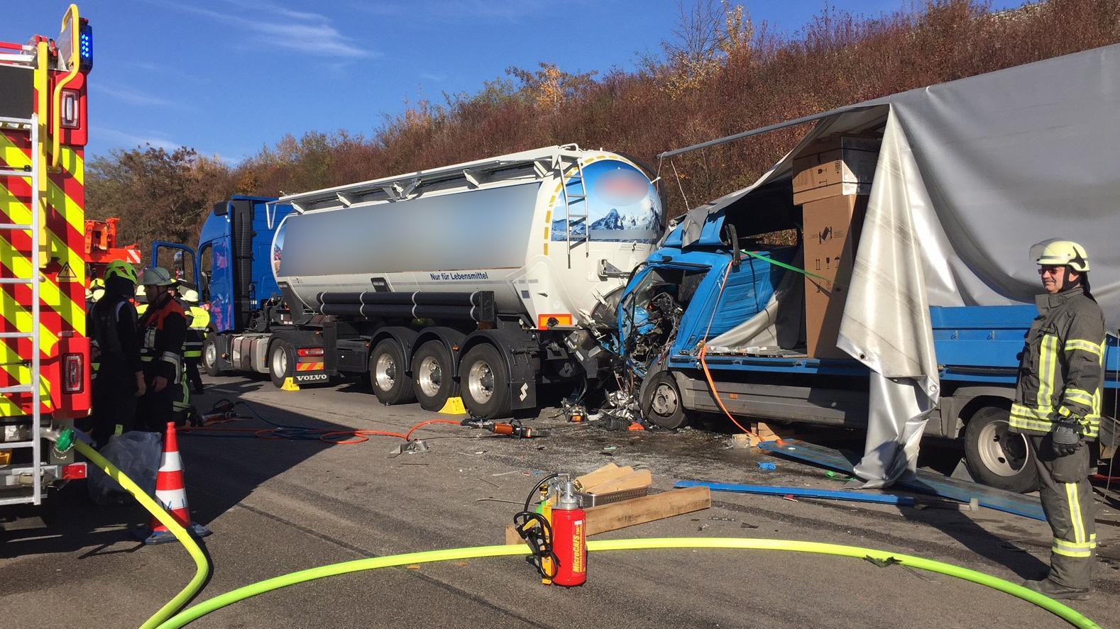 Einsatzkräfte der Feuerwehr, im Hintergrund zwei der drei aufeinander gefahrenen Lastwagen.