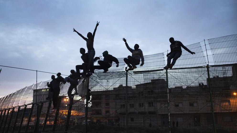Abendbild: Migranten aus dem Südsahararaum beim Überwinden des Grenzzauns der spanischen Enklave Ceuta. Einige hangeln sich noch am Zaun hoch, andere sind bereits oben und recken jubelnd die Arme in die Höhe. | Bild:picture alliance / AP Photo Anbieter:picture alliance/AP  Fotograf:Santi Palacios