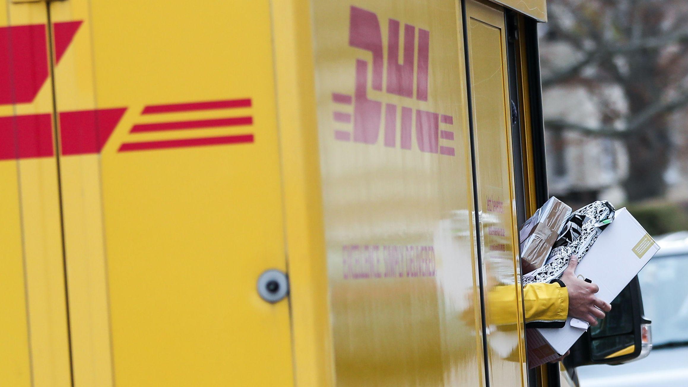 Ein DHL-Paketzusteller verlässt mit mehreren Sendungen sein Fahrzeug.