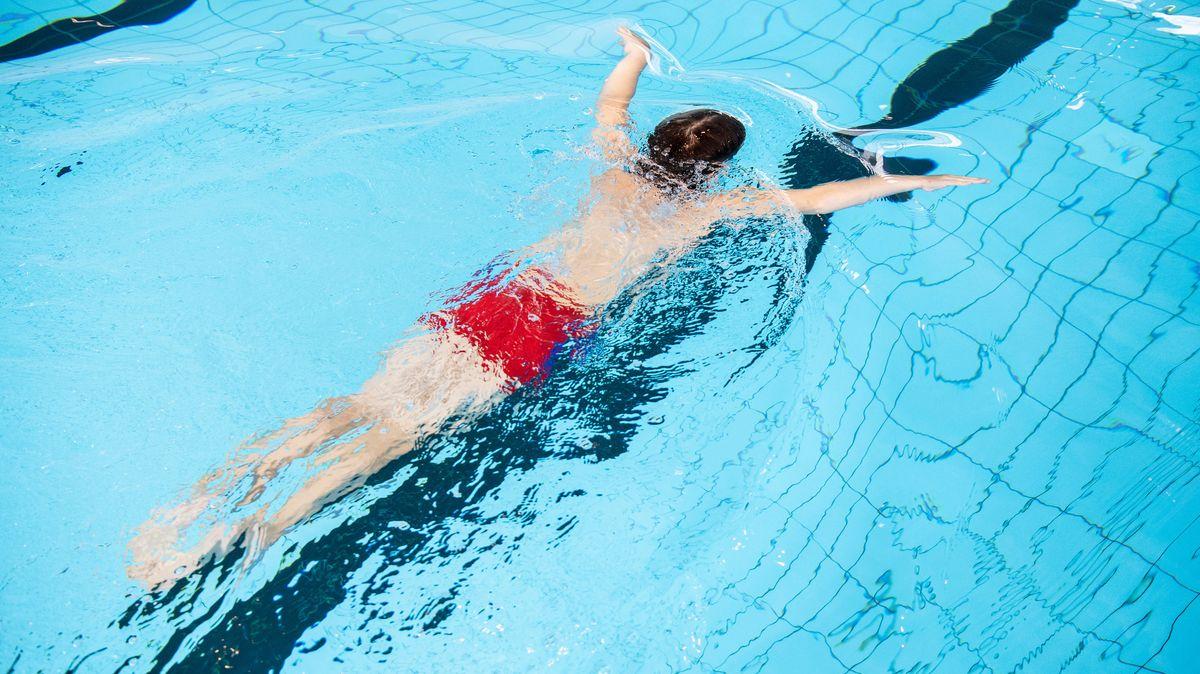 Ein Junge zieht in einem Schwimmbad seine Bahnen.