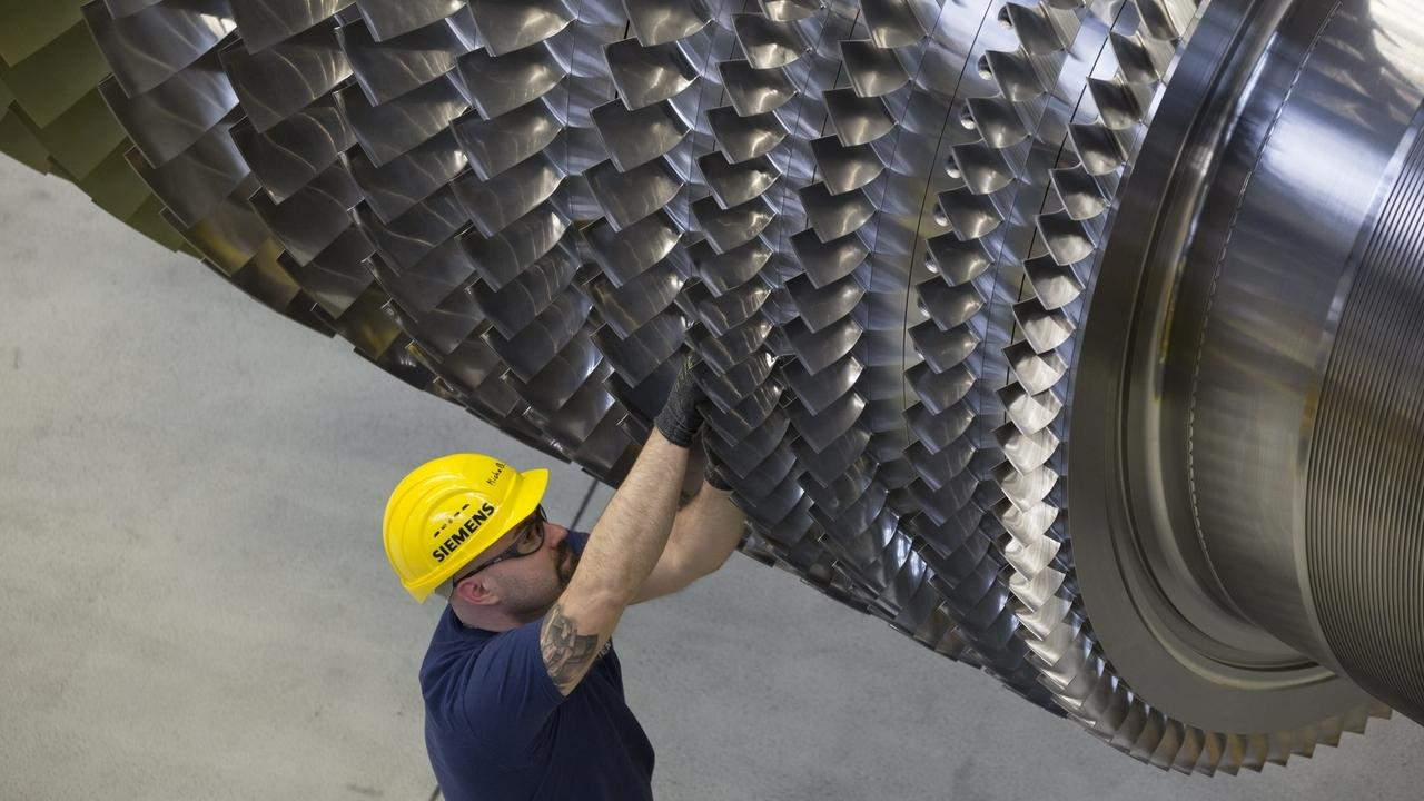 Ein Siemens-Arbeiter mit einer Gasturbine