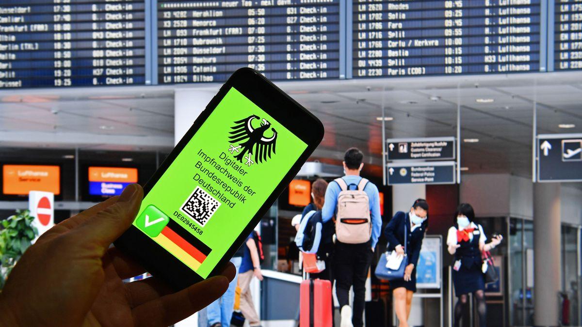 Ein digitaler Impfausweis wird am Flughafen in die Kamera gehalten.