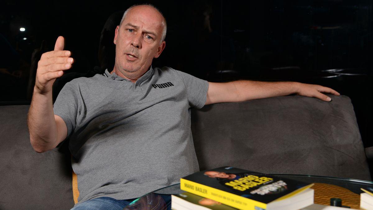 Mario Basler lehnt in einem Stuhl, vor ihm ein Stapel Bücher.