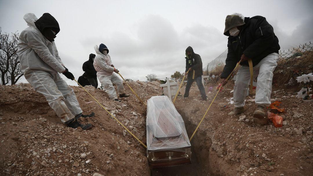 Mexiko: Arbeiter legen einen Sarg in ein Grab eines städtischen Friedhofs.