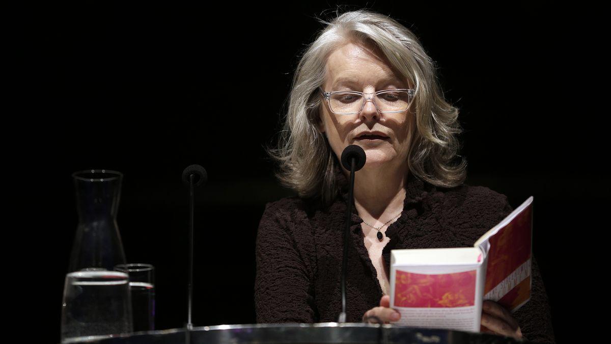 Marlene Streeruwitz liest ein Buch und spricht dabei in ein Mikrofon vor sich.