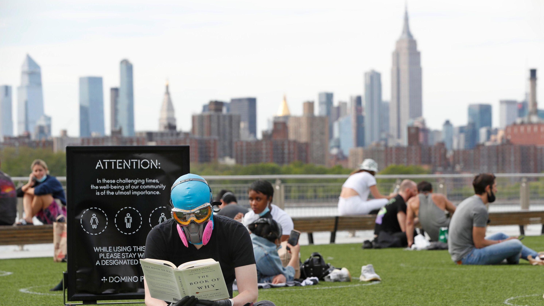 New York: Ridley Goodside trägt eine Schutzbrille und eine Schutzmaske, während er im Domino Park im Stadtteil Brooklyn und ein Buch liest.