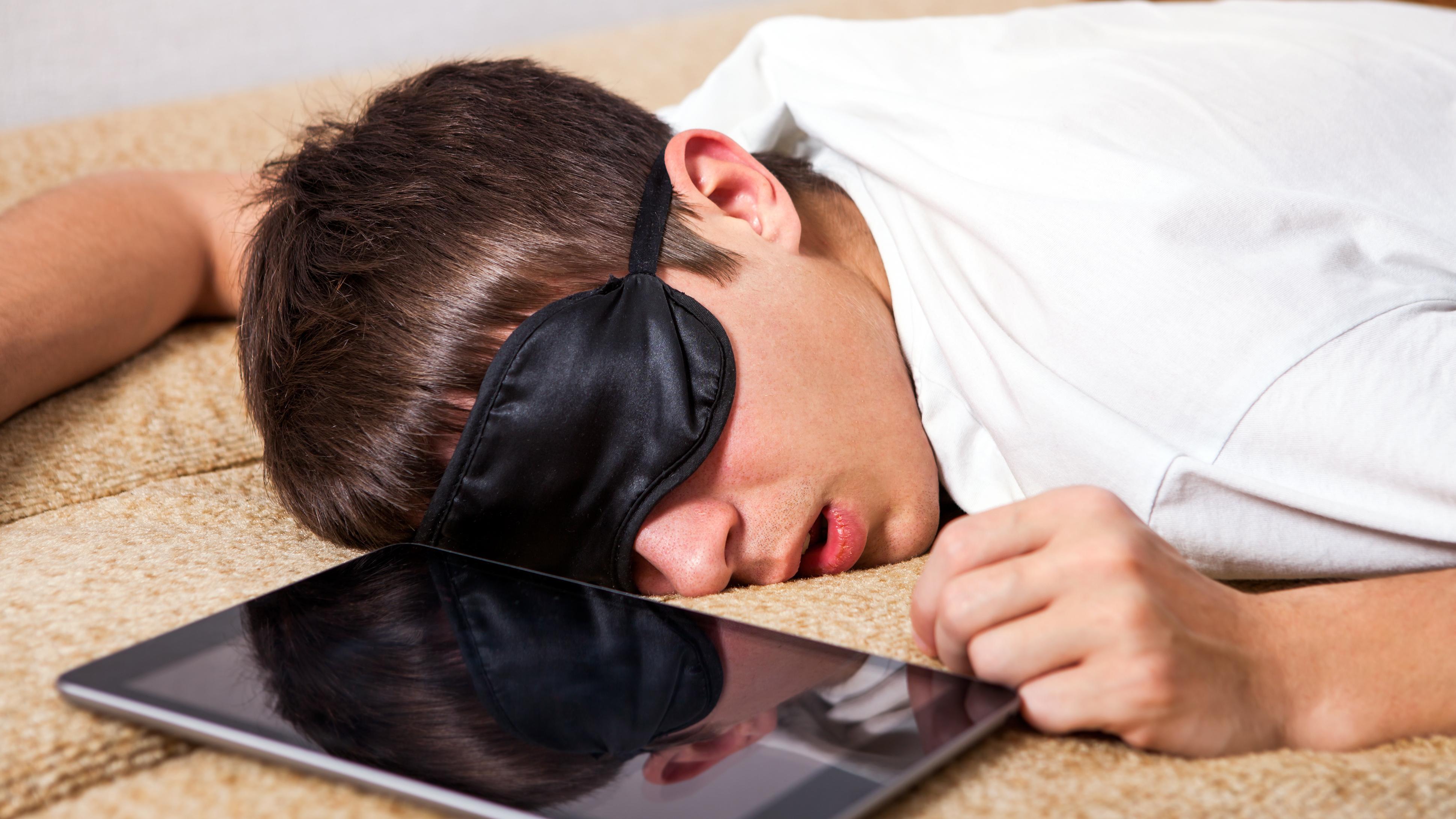 Junger Mann schläft neben einem Tablet