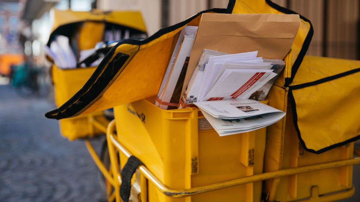 Ein Fahrrad der Post steht mit einem Bündel an Briefen vor einem Haus.