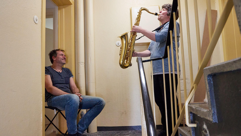 Eine Saxophonistin gibt im Treppenhaus ein Solo-Konzert für ihren Nachbarn, der auf einem Hocker in der Wohnungstür sitzt